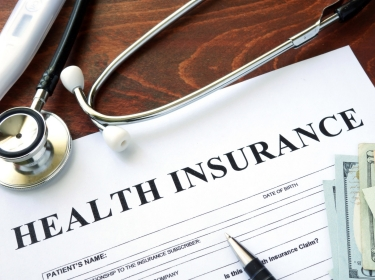 Health insurance form, stethoscope, thermometer, and dollar bills on a wooden table