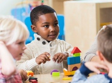A boy in preschool playing with building blocks with classmates