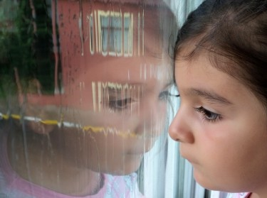 A young girl looks out of a window