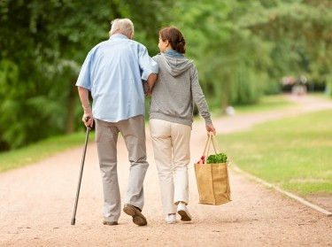 Female caregiver carrying groceries and walking along a dirt path with an elderly man