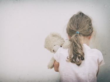 A young girl holding a teddy bear
