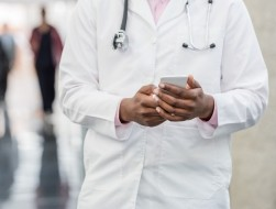 Close up of a doctor looking at his phone
