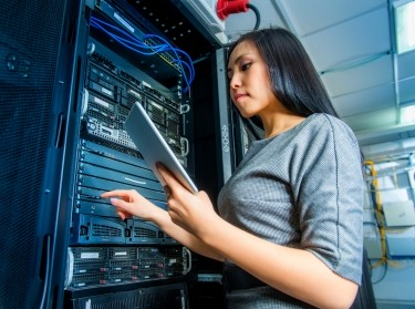 A female systems engineer working on a computer server