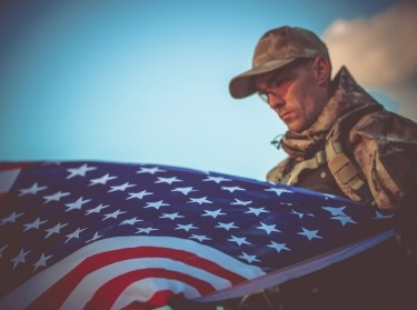 Young military veteran with American flag in the foreground