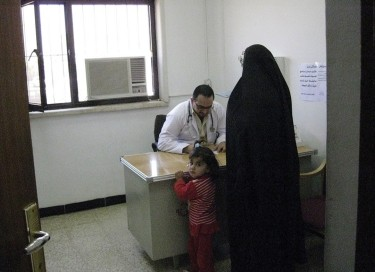 A doctor sits behind a desk while speaking to a woman and her young child
