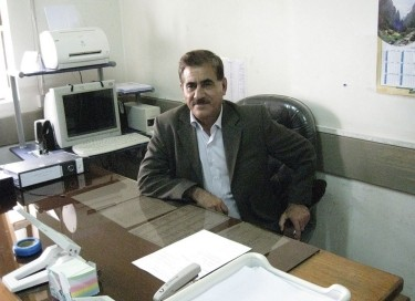 A doctor sits at his desk