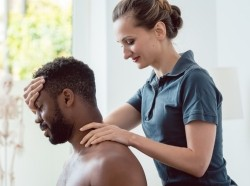 Chiropractor adjusting a male patient, photo by kzenon/Getty Images