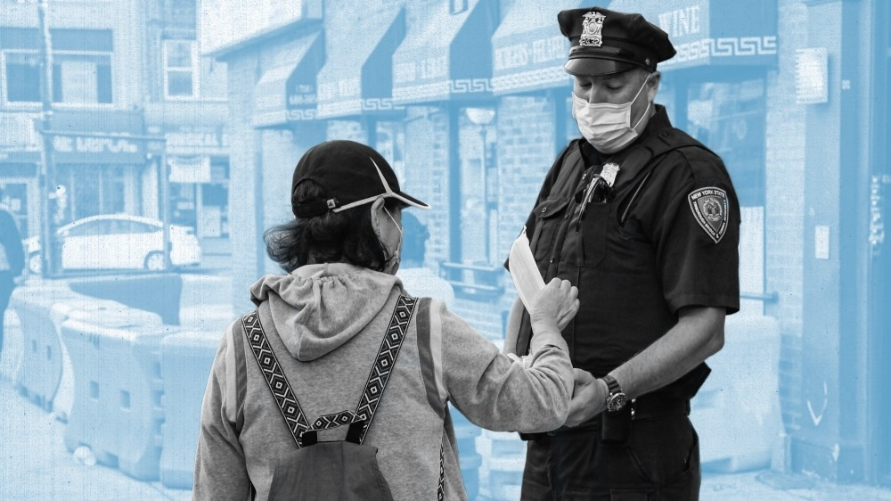 A police officer distributes a face mask to a passerby on a city street