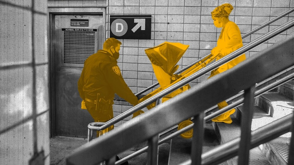 A police officer helps a woman with a baby stroller on the stairs to a subway platform