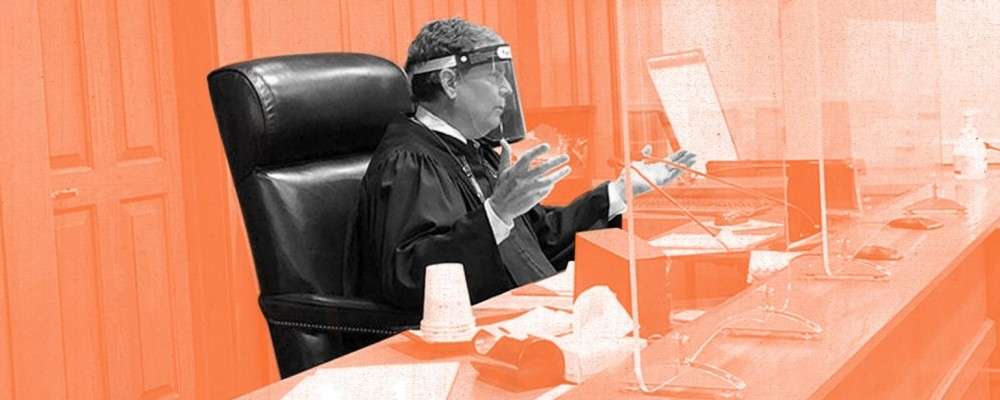 A judge wearing a face shield sits at the bench behind plexiglass dividers