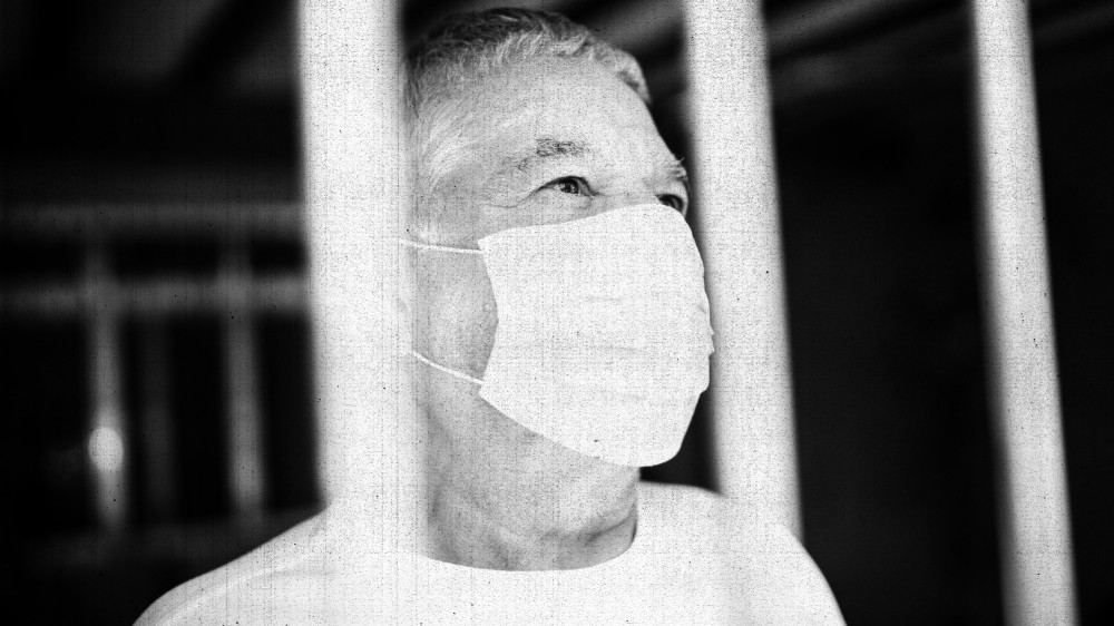 A man wearing a mask behind bars