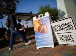 People walk past a COVID-19 vaccination center near the Santa Fe International Bridge, in El Paso, Texas, May 7, 2021, photo by Jose Luis Gonzalez/Reuters