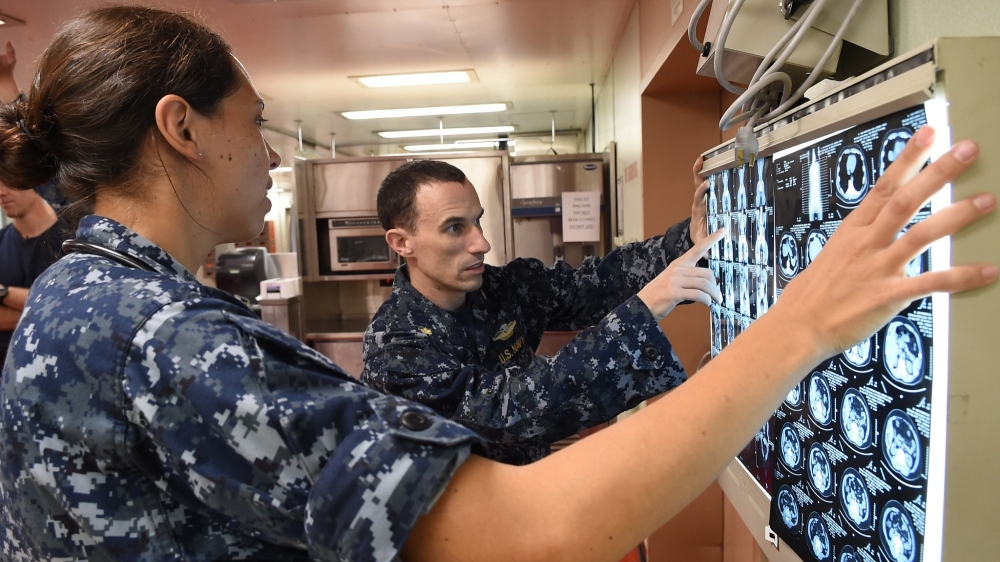 Two members of U.S. Navy personnel examine a series of brain scans