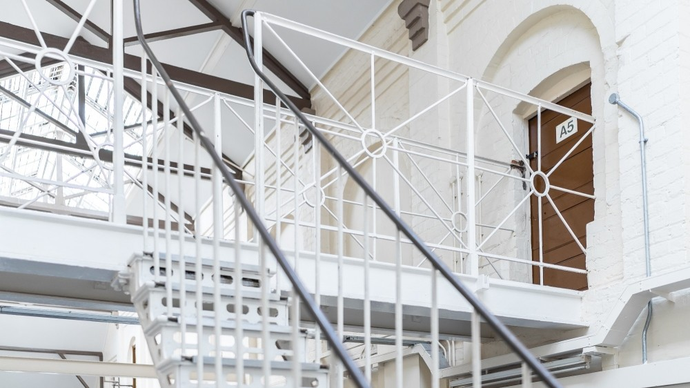 Old Victorian prison landing wing with bars and staircase of high security  immigration detention centre with brown cell door in England bright daylight