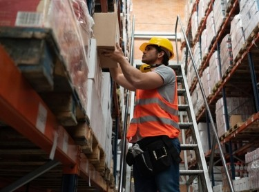 A warehouse worker wearing a hardhat and high visibility vest stacking boxes. Photo by andresr / Getty Images