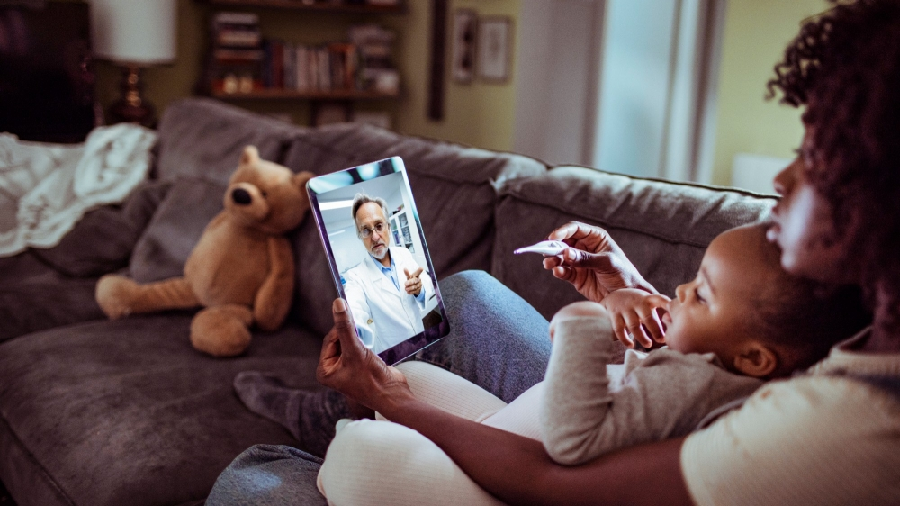 Close up of a mother and daughter consulting with their doctor over a video call on their digital tablet