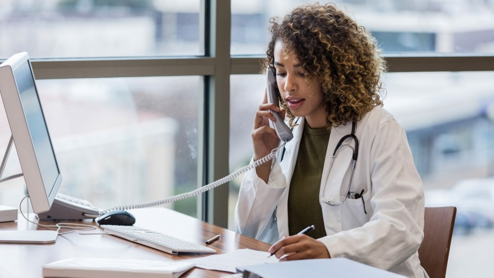 A mid adult female doctor, sitting in her office, uses the landline to make phone calls.