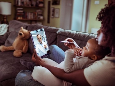 Close up of a mother and daughter consulting with their doctor over a video call on their digital tablet, photo by Geber86/Getty Images
