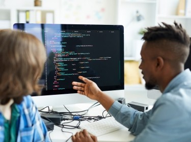 Busy young interracial colleagues analyzing computer code on computer: African man pointing at monitor and asking coworker in office, photo by pressmaster/Adobe Stock