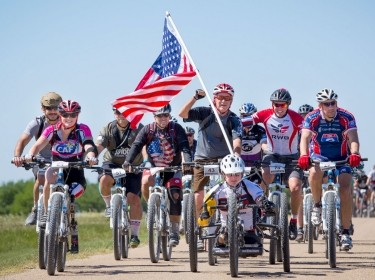 Group of adults riding bikes together with an American flag attached to the front bike
