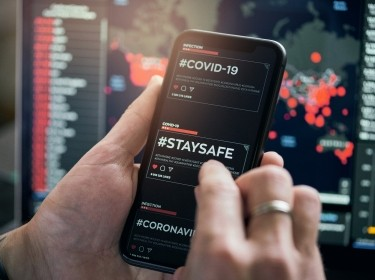 COVID-19 content displayed on a mobile phone, photo by da-kuk/Getty Images