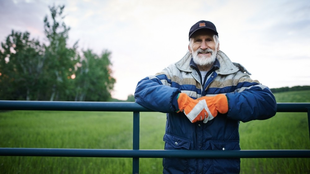 Older man standing at a farm fence and smiling at the camera. Photo by AJ_Watt/Getty Images