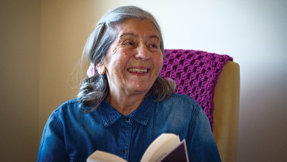 Elderly woman holding a book and smiling