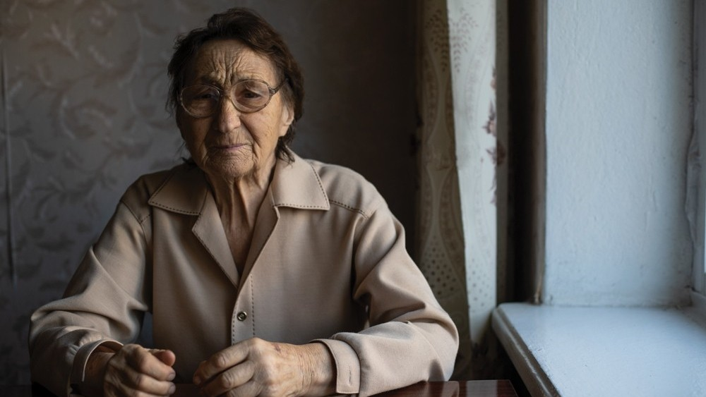 A very old woman wearing glasses and looking at the camera