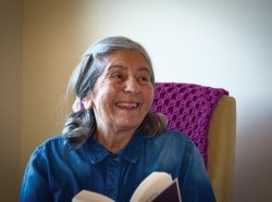 A senior woman smiling and holding a book, photo by the Weinberg Center