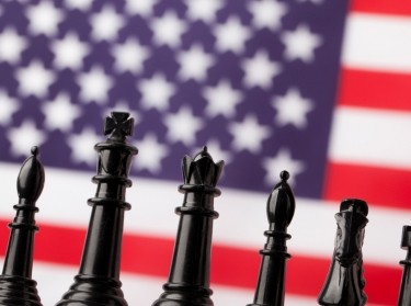 Chess pieces in front of an American flag