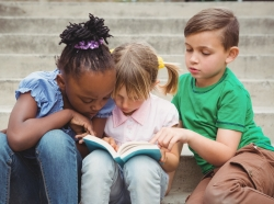 Three children sitting on steps and reading a book