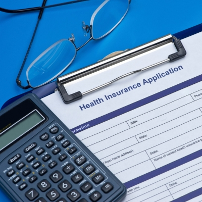 Health insurance application with glasses and calculator