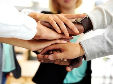 Group of people stacking their hands together