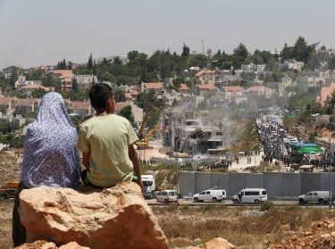 Palestinians watch Israeli heavy machinery demolishing vacant apartment blocs by order of Israel's high court, in the West Bank Jewish settlement of Beit El near Ramallah July 29, 2015