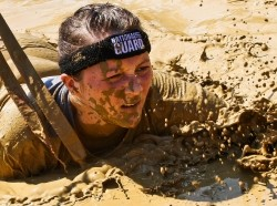 2nd Lt. Mary Kauffman, Ohio Army National Guard, crawls through mud during the Warrior Dash Aug. 11, 2013, in North Lawrence, Ohio