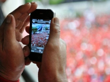 A person uses a smartphone to photograph a Red Shirt rally in Bangkok, Thailand