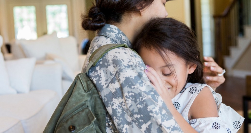Female soldier hugs her daughter, photo by SDI Productions/Getty Images