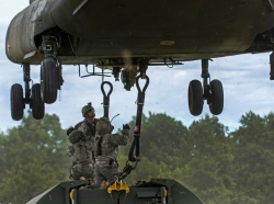 Army reservists hook a bay bridge to a CH-47 Chinook helicopter using a sling harness during a slingload training operation at Fort Chaffee, Arkansas