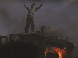 A man stands on a buring military vehicle