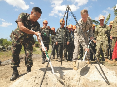 Philippine Army Lt. Col. Henry Bellan (left) and U.S. Army Lt. Col. John Garrity (right) bury a time capsule during a groundbreaking ceremony in San Narciso, Philippines, March 18, 2013