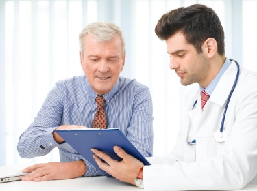 Older man consulting with male doctor