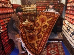 Afghan carpet salesmen fold a carpet after showing it to customers at a shop in Kabul
