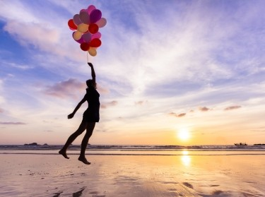 Dreaming woman flying in the sky lifted by helium balloons