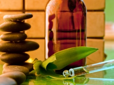 Alternative medicine: hot stones, medicine bottle, herbs, and eyedropper