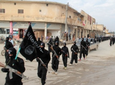 Fighters of al-Qaeda linked Islamic State of Iraq and the Levant carry their weapons during a parade at the Syrian town of Tel Abyad January 2, 2014