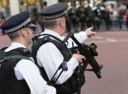Armed police officers on guard near Buckingham Palace, London, for Trooping the Colour, June 16, 2012