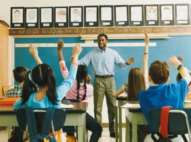 Teacher standing in front of a classroom of students with hands raised