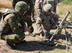 U.S. soldiers show an Estonian soldier how the mortar system operates during a call for fire live exercise in Estonia, Aug. 7, 2015