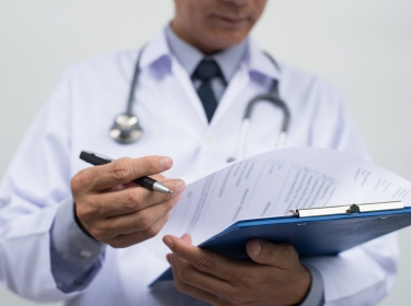 A doctor wearing a white coat holding a clipboard