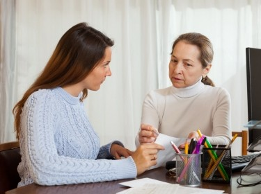 A young woman speaking to a social worker in an office